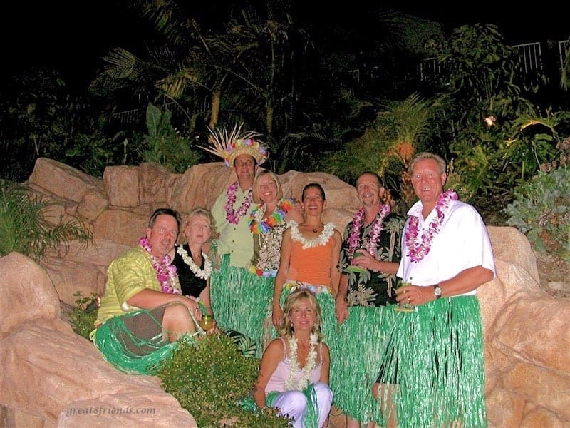 Eight people posing with grass skirts and leis on at a Luau dinner party.