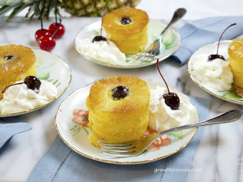 4 individual Pineapple Upside Down Cakes with cherries on small plates