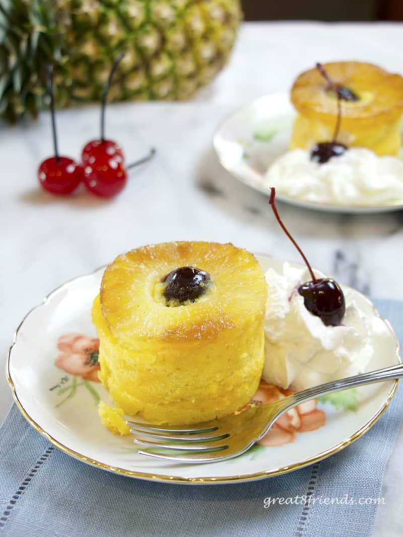 An individual Pineapple Upside Down Cake on a plate with a fork and a dollop of whipped cream with cherries.