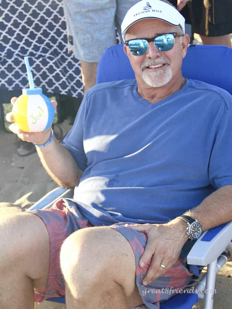 Joel sitting at the beach with his beach ball cup.