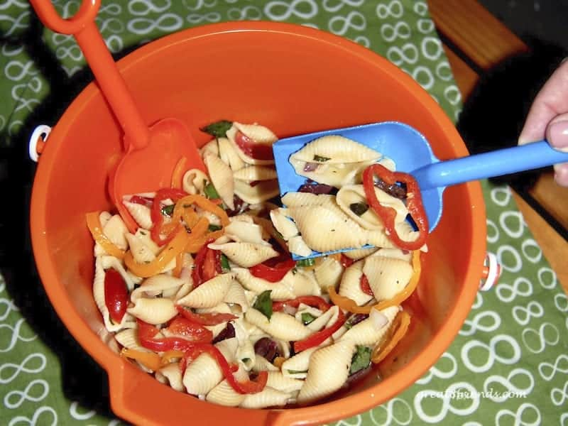 Shell pasta salad in an orange plastic beach pail.