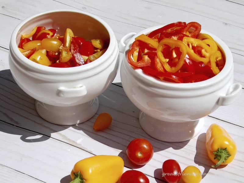 sliced pear tomatoes and sweet orange and yellow peppers in white bowls