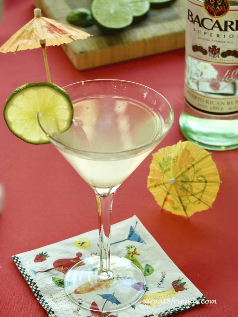 Rum Daiquiri in a martini glass garnished with a lime slice and paper umbrellas.
