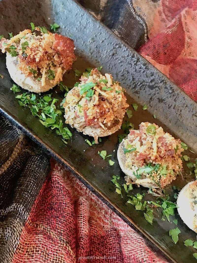Individual mushrooms stuffed with prosciutto and parmesan served on a rectangular platter as an appetizer.