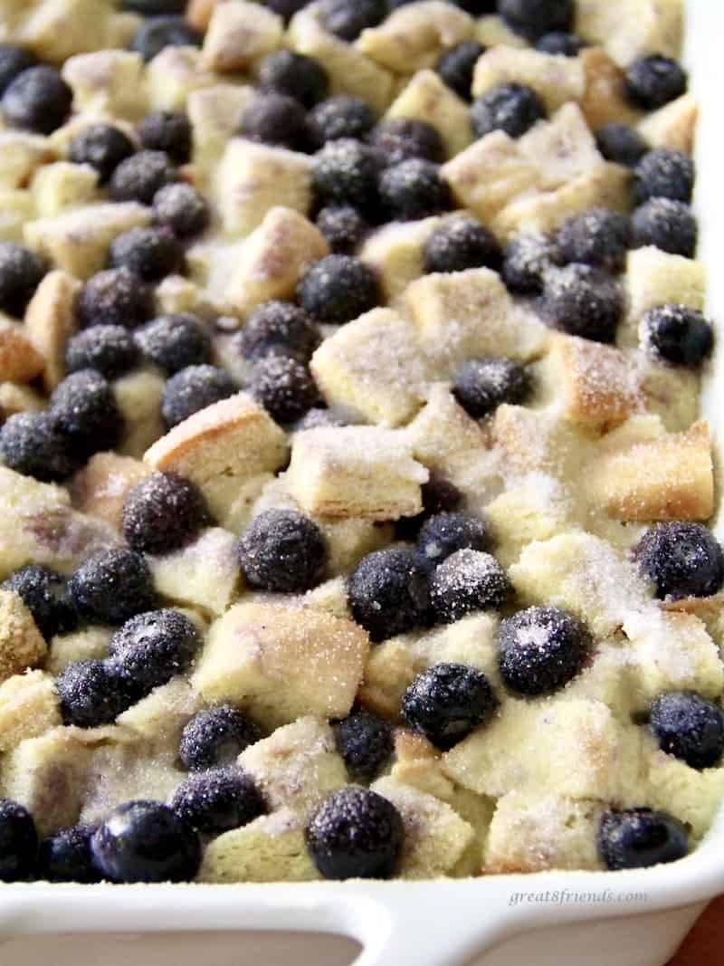 A sprinkle of sugar adds a delicious bit of sweetness to this blueberry bread pudding ready to be baked.