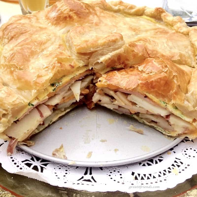 Baked and cut brunch torte showing the insides of potatoes, eggs and onions.