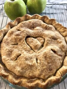 Baked apple pie with a heart cut in the top crust.