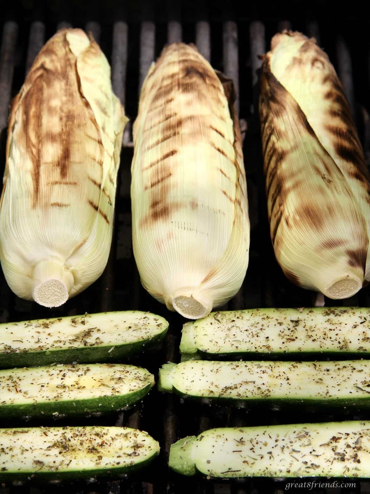 Corn in the husk and seasoned cut zucchini grilling on the backyard grill.