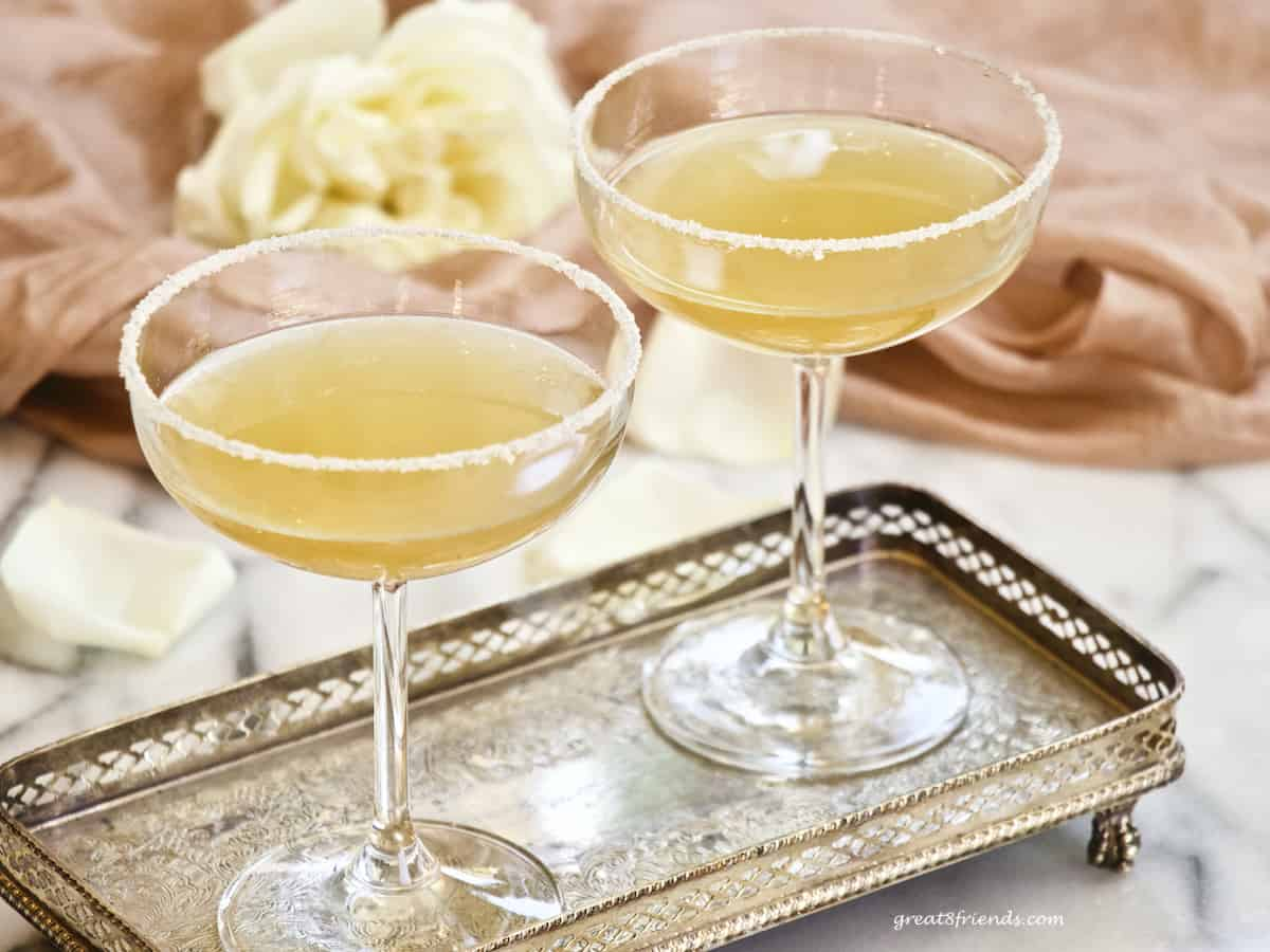 Two sidecar cocktails in coupe glasses on a silver tray with a white rose on pink in the background.