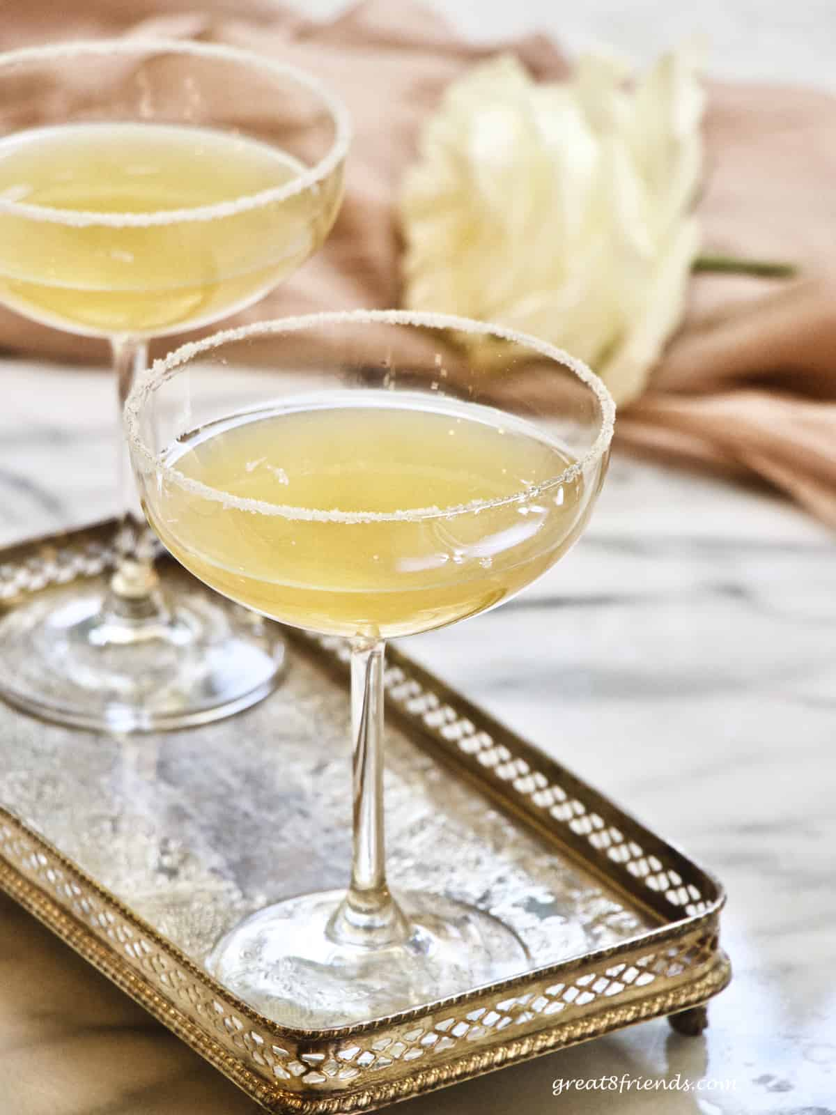 Two sidecar cocktails in couple glasses on a silver tray with a white rose on pink in the background.
