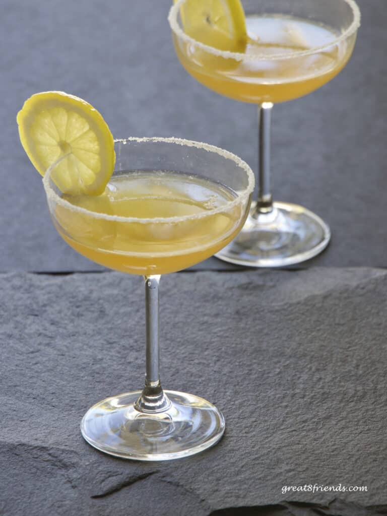 Two sidecar cocktails in coupe glasses garnished with lemon slices.