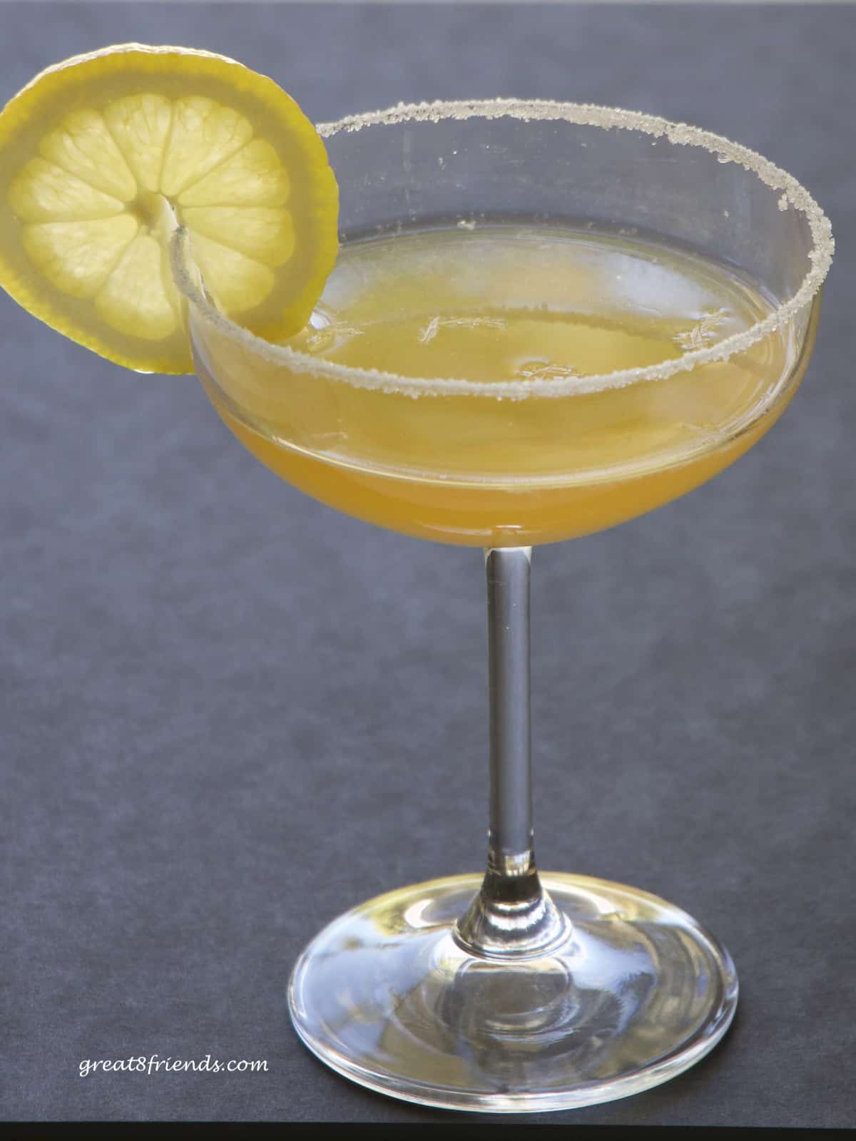 A sidecar cocktail in a coupe glass garnished with a slice of lemon.