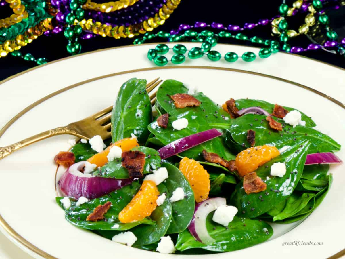 Spinach Salad with red onion, orange slices, feta cheese and bacon. Mardi Gras beads in the background.