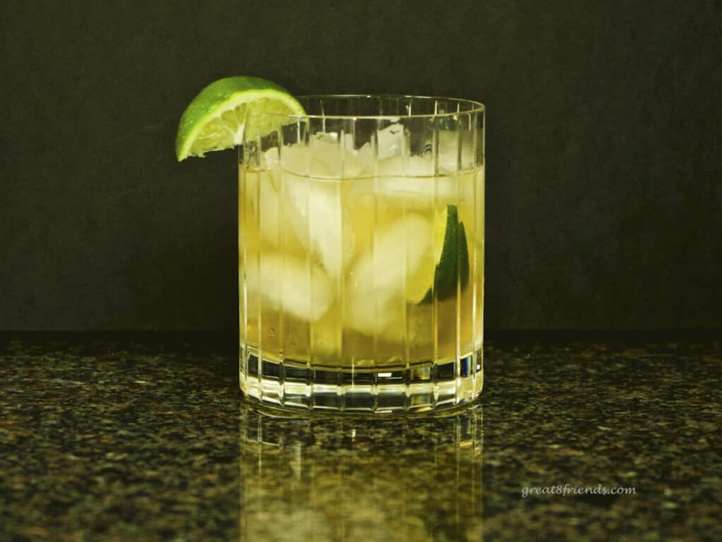 A cocktail in a double old-fashioned glass garnished with a wedge of lime. Gifts for Guys.