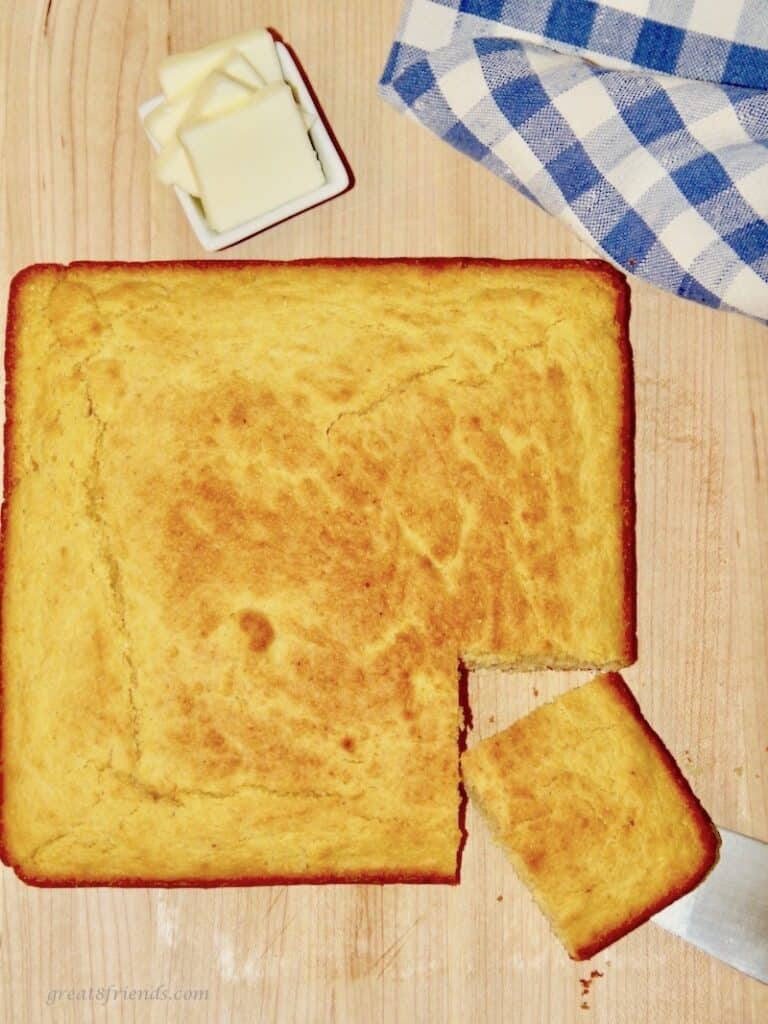 Overhead shot of a square cornbread with one piece cut with butter and a blue checked napkin on the side.