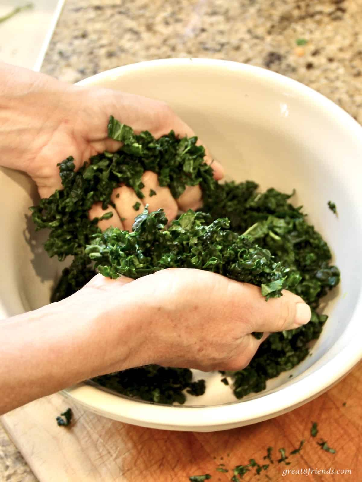 A bowl of torn tuscan kale leaves that are being massaged with someones hands.