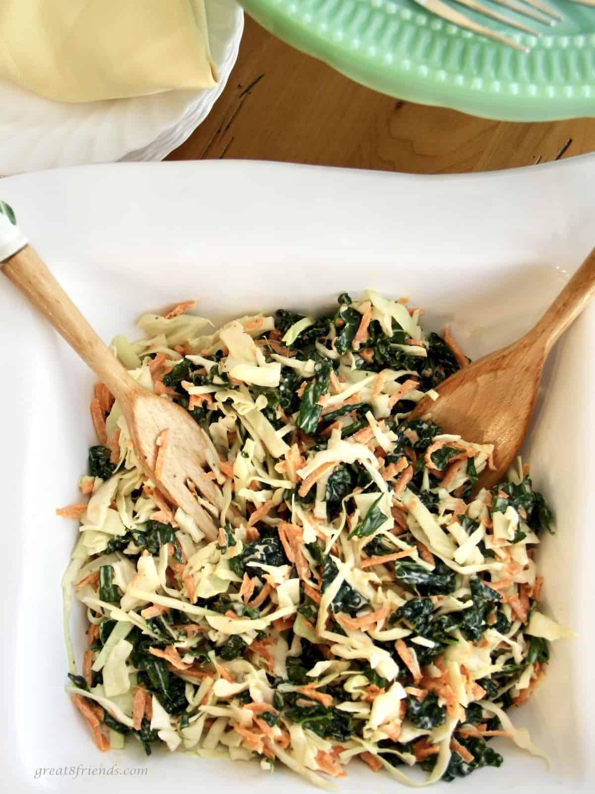 Kale slaw salad in a white square bowl with a wooden salad serving spoon and fork.