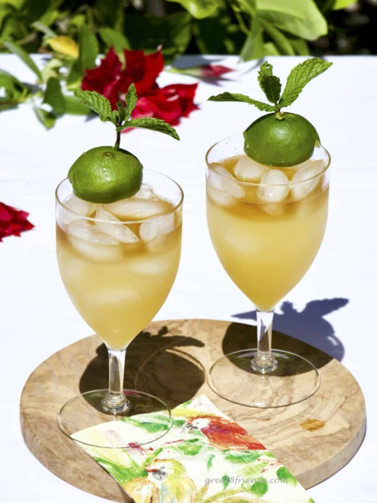 Two Mai Tais in stemmed iced tea glasses on a round wooden board with red flowers in the background.