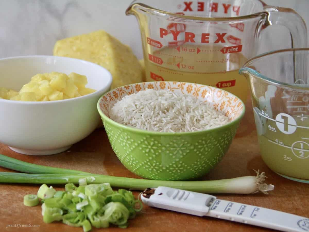 Ingredients for making pineapple rice including green onions, chicken broth, pineapple juice and red pepper flakes.