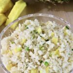 Glass bowl of pineapple rice salad with some chunks of pineapple in the background.