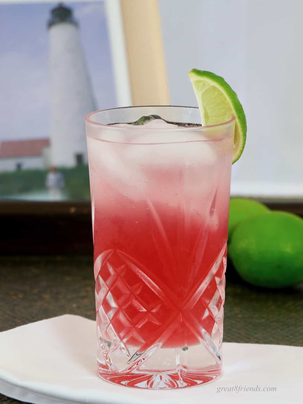 Photo of a red cocktail in a highball glass garniished with a wedge of lime.