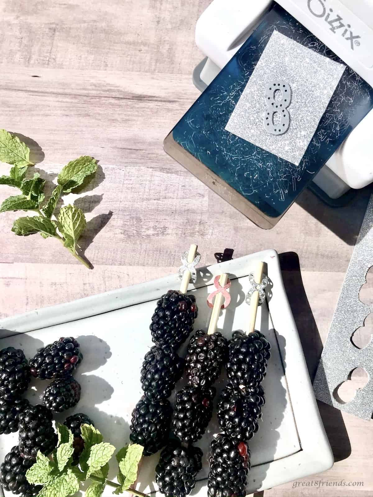 Fresh blackberries on a stick with a paper number eight on the end with a paper cutting machine on the side.
