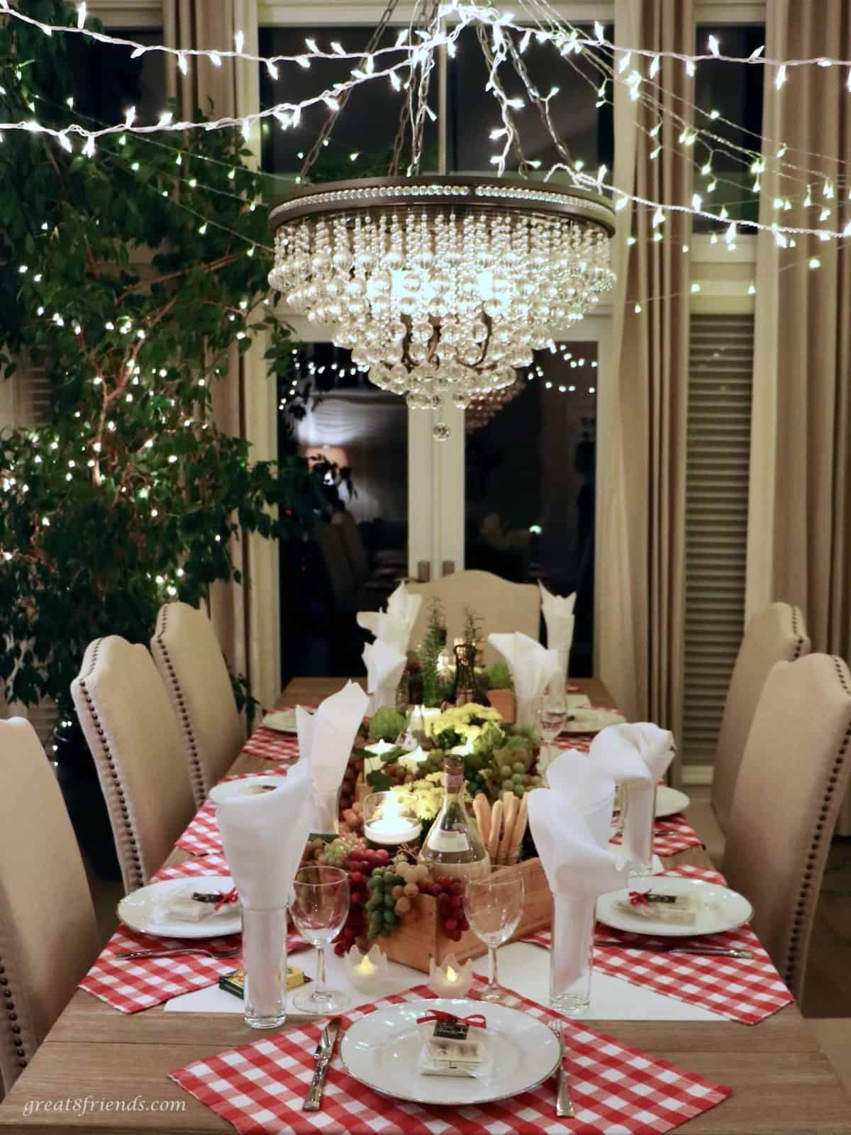 Table set for an Italian dinner with a chandelier over the table.