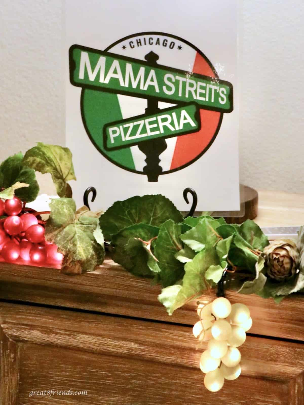 Mama Streit's Pizzeria sign on a mantle with decorative green and red grapes with lights.
