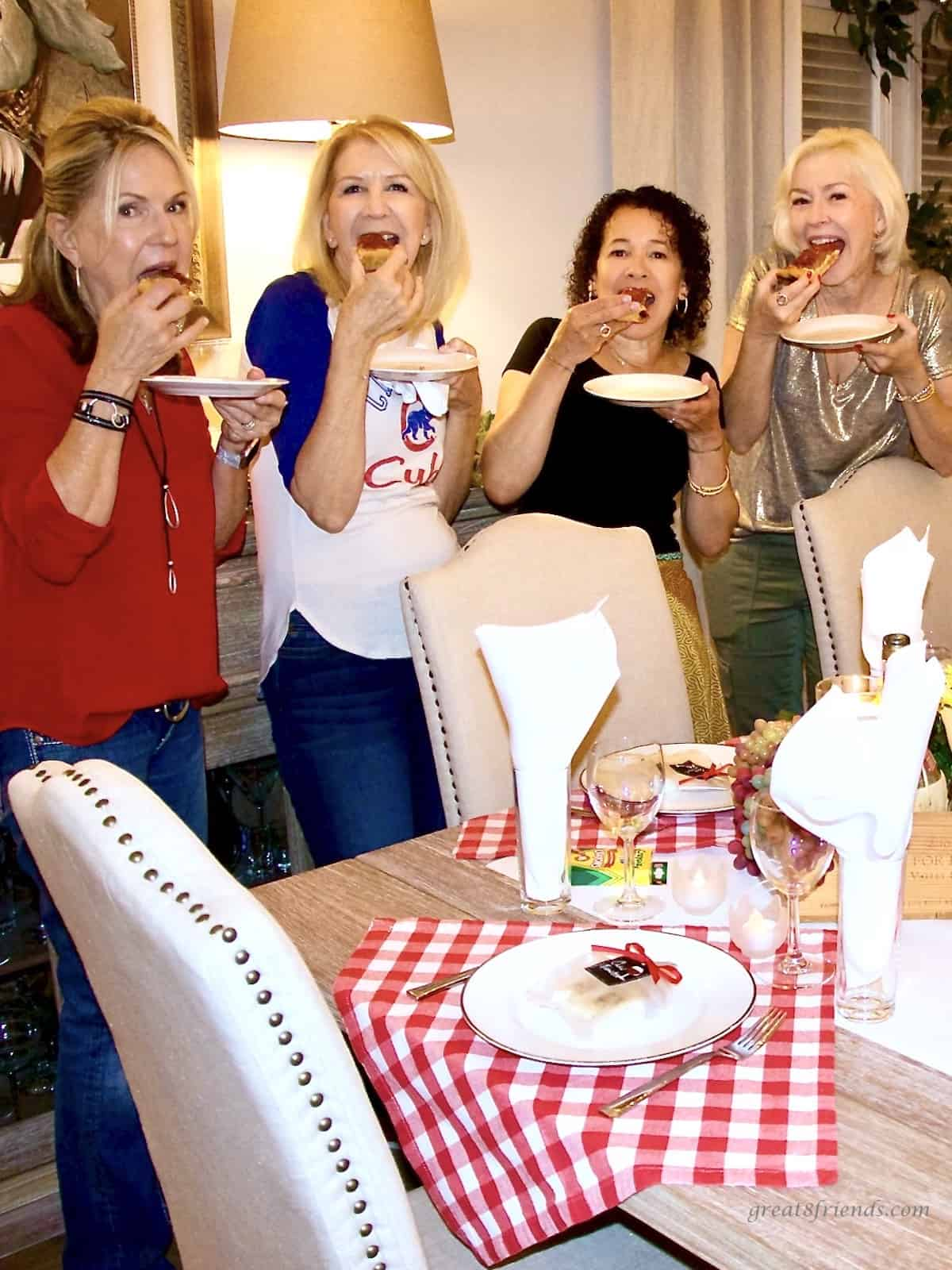 Four women eating each eating a piece of pizza standing in a dining room with a table set for an Italian meal.