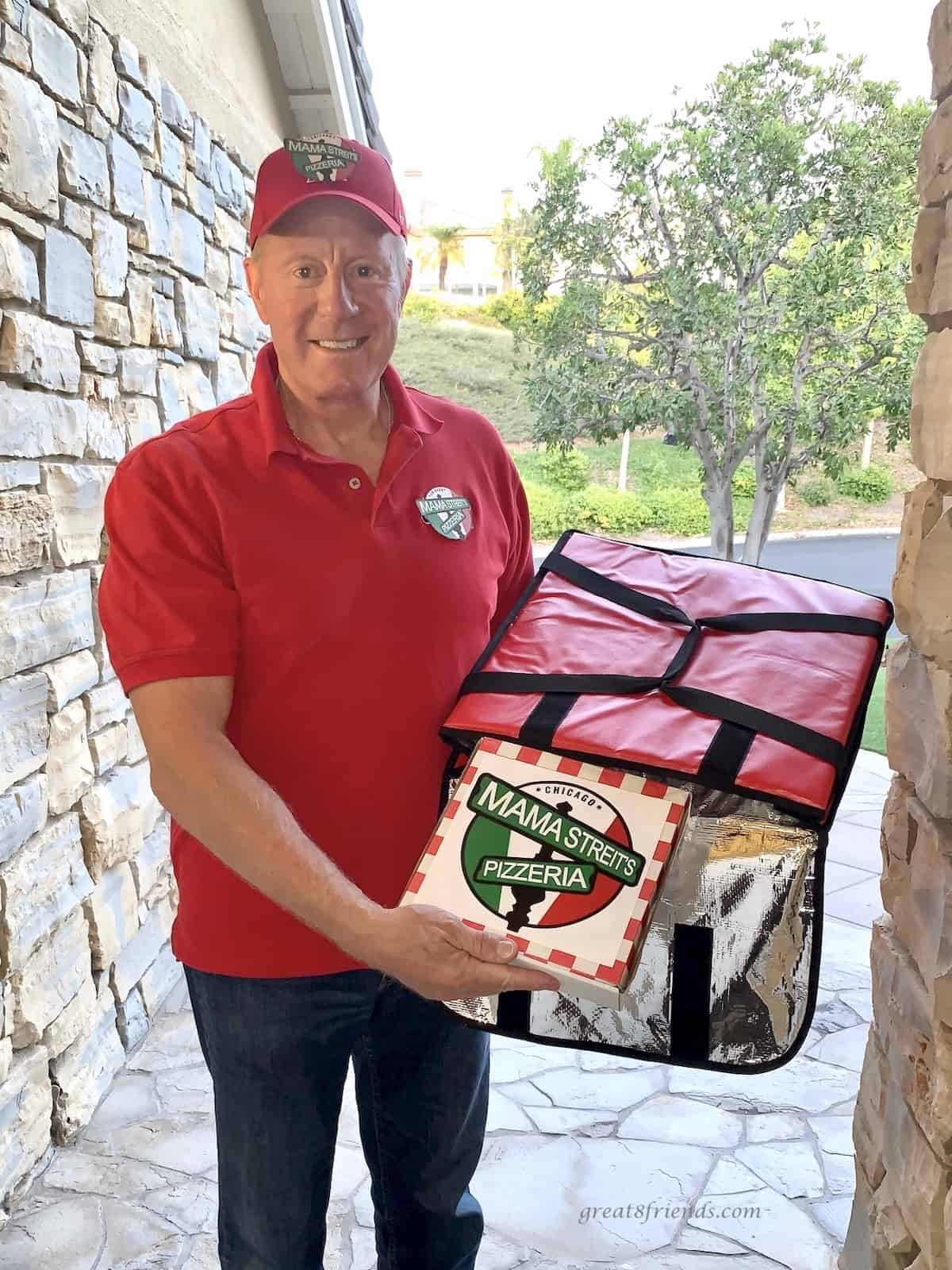 A man at a front door delivering pizza from a pizza bag.