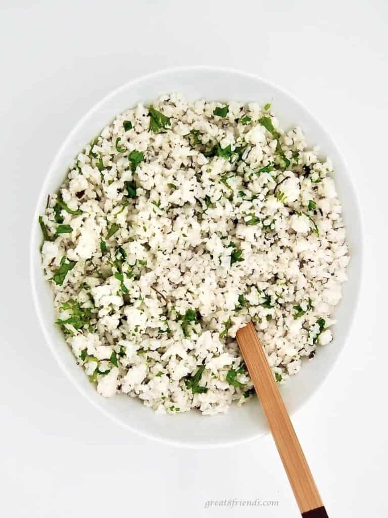 Coconut Lime Cilantro Rice in a white bowl with a wooden spoon.