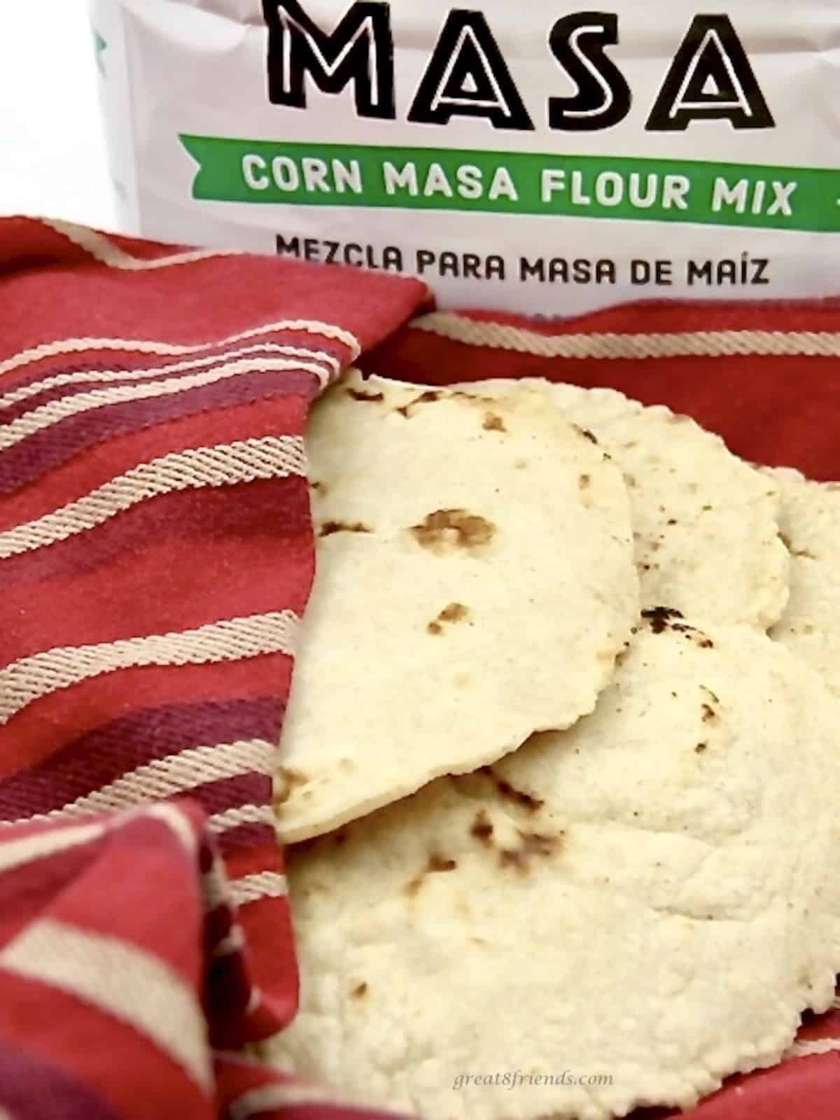 A red towel holding several corn handmade tortillas with a bag of masa flour mix in the background.