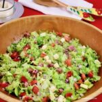 Italian Chopped Salad in a wooden bowl with salad servers in the background.