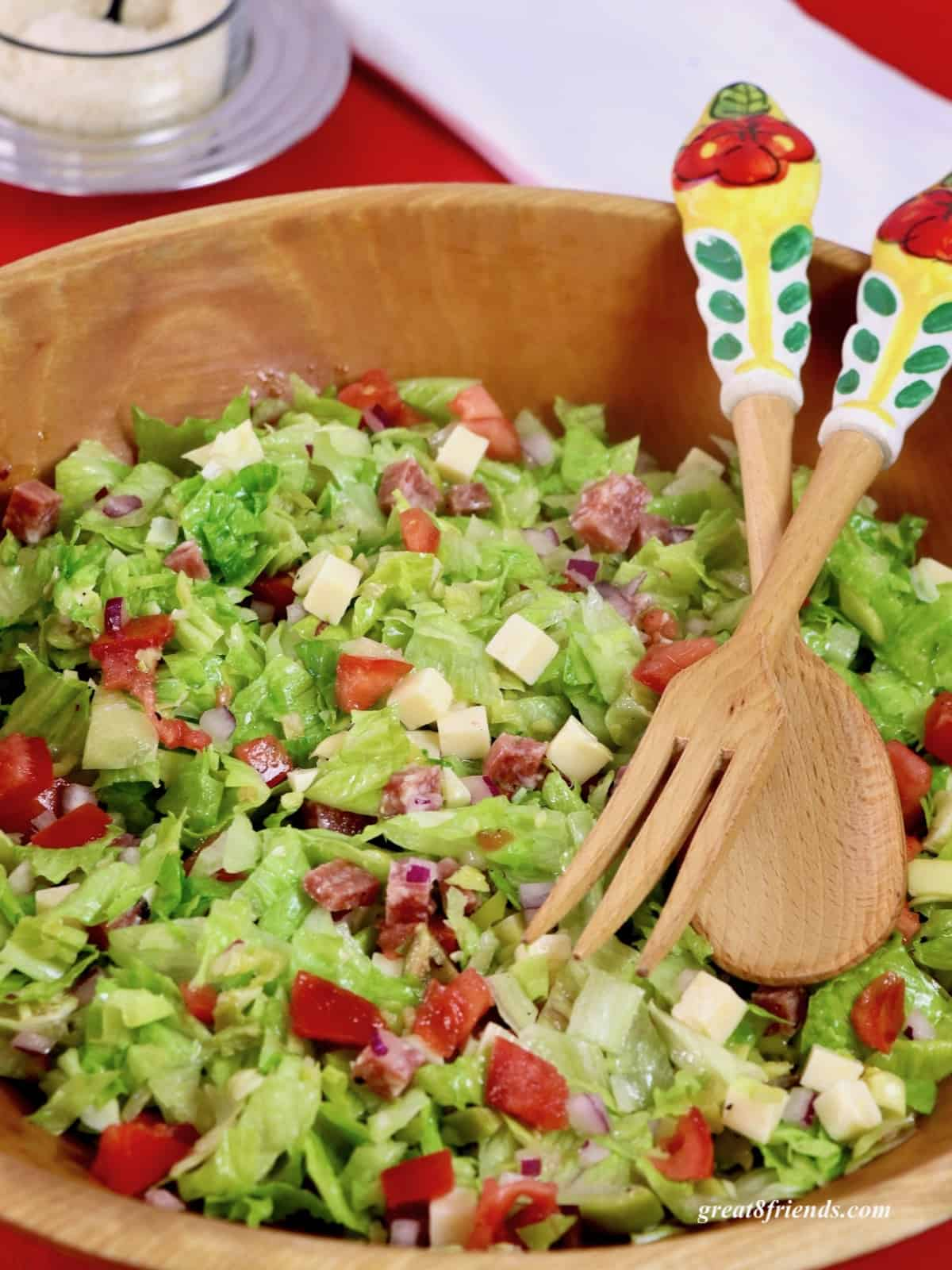 Italian Chopped Salad in a wooden bowl with salad servers.
