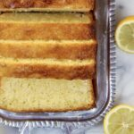Sliced loaf of lemon ricotta pound cake on a silver platter with a cut lemon on the side.