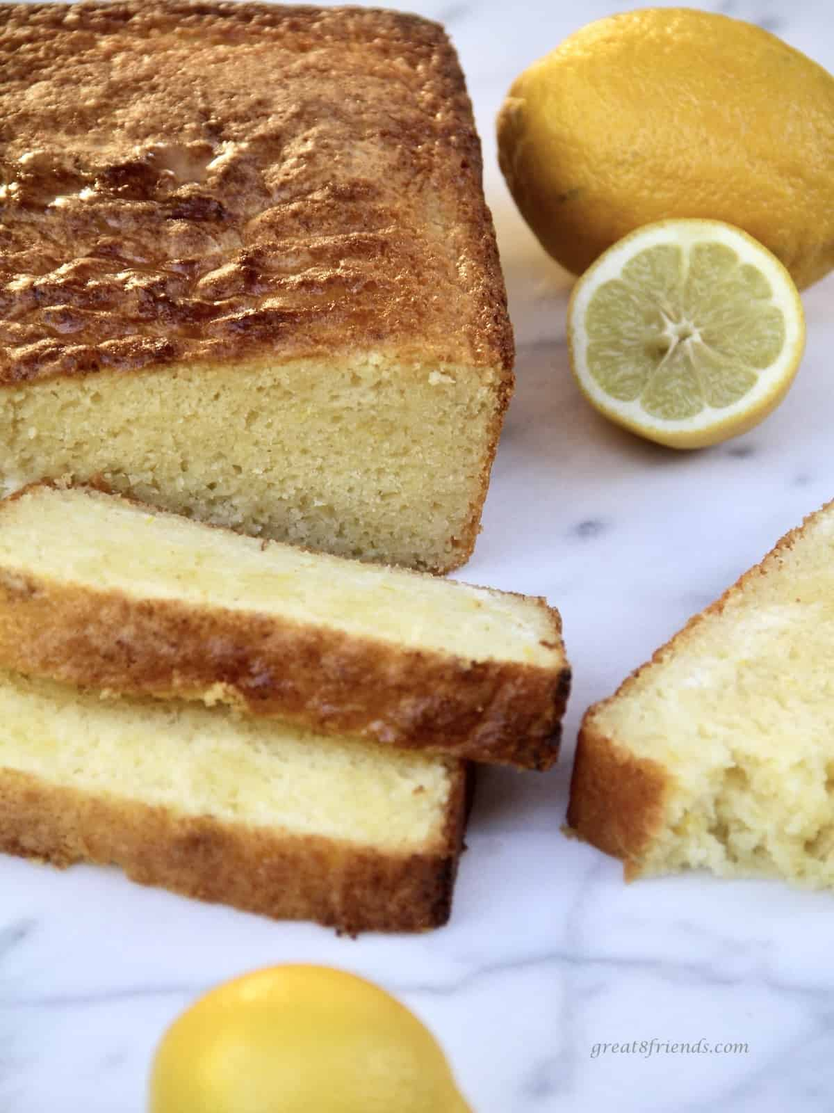 Lemon pound cake partially sliced with lemons on the side.