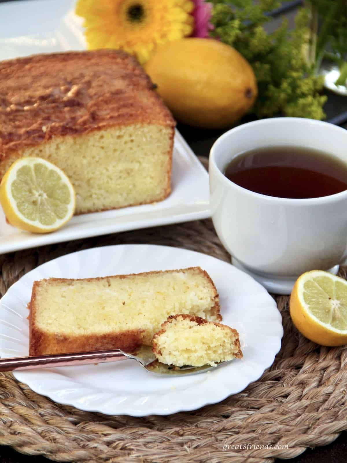 Sliced lemon ricotta pound cake served with a cup of coffee.