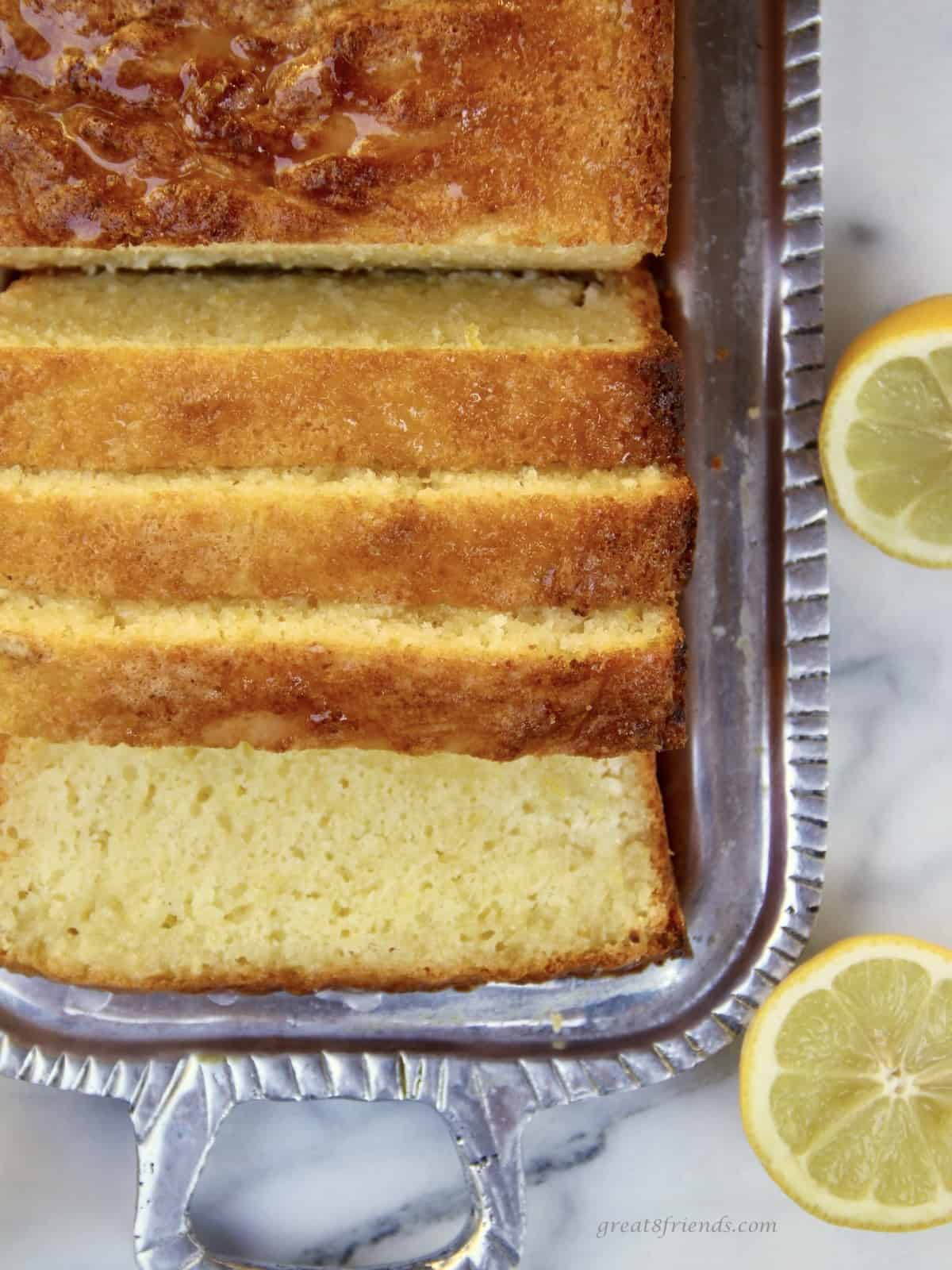 Sliced cake on a silver platter with  a lemon cut in half on the side.