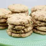 Several nut shortbread cookies stacked on a light green platter.