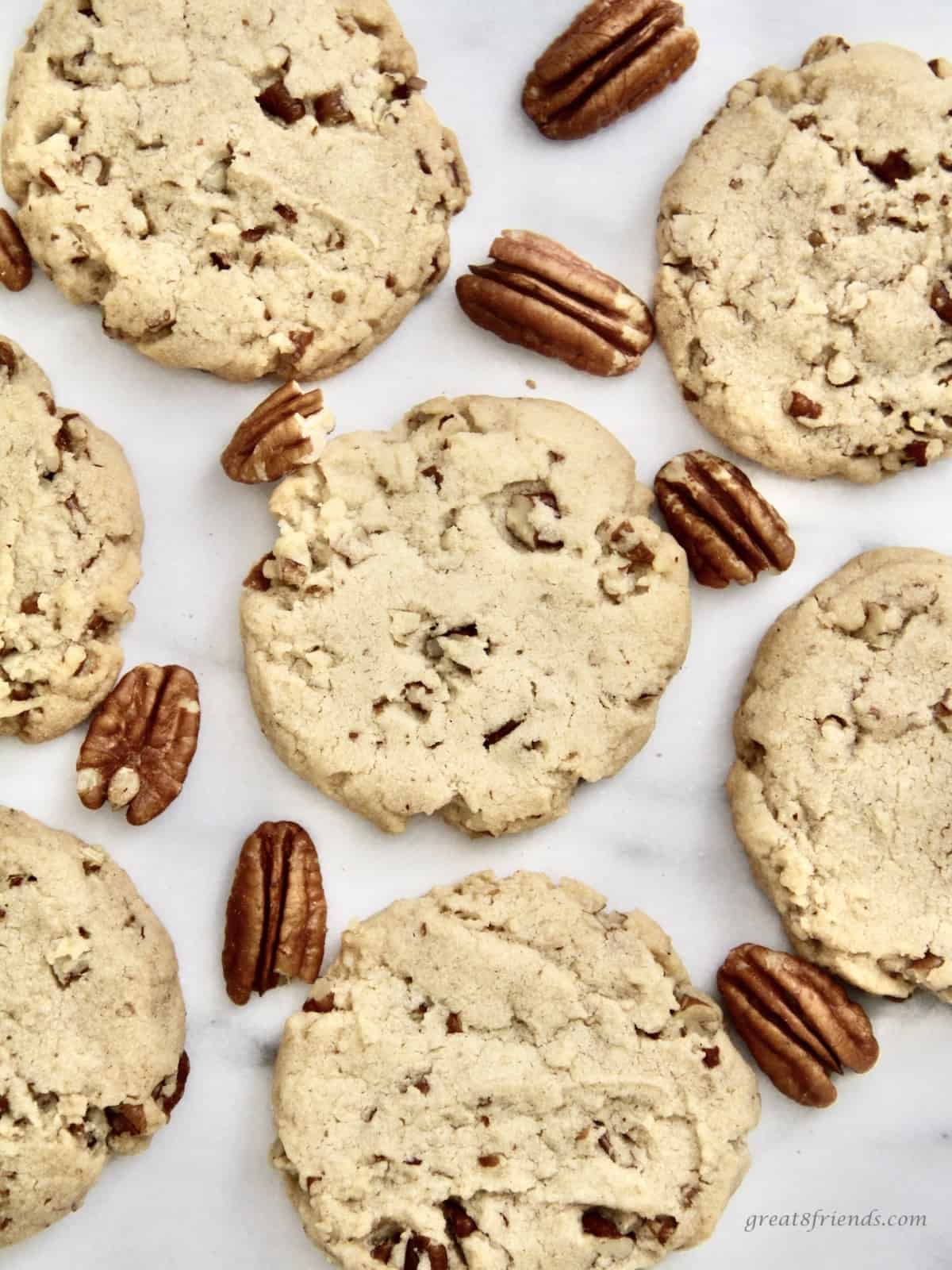 Pecan Sandies cookies on a white marble surface with a few whole pecans alongside the cookies.