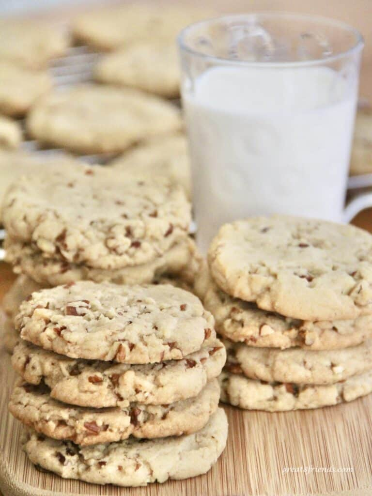 This nutty Pecan Sandies cookies are stacked in front of a glass of milk.