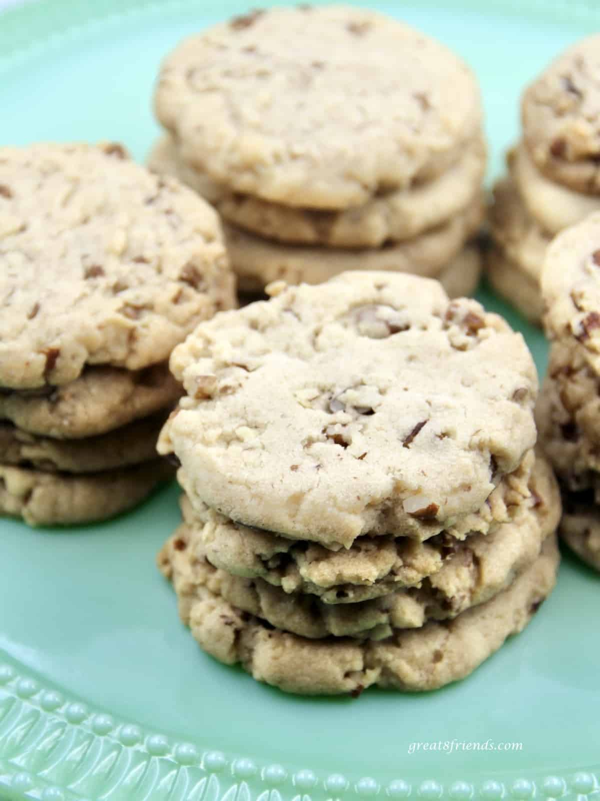 Pecan cookies stacked on a green cake plate.