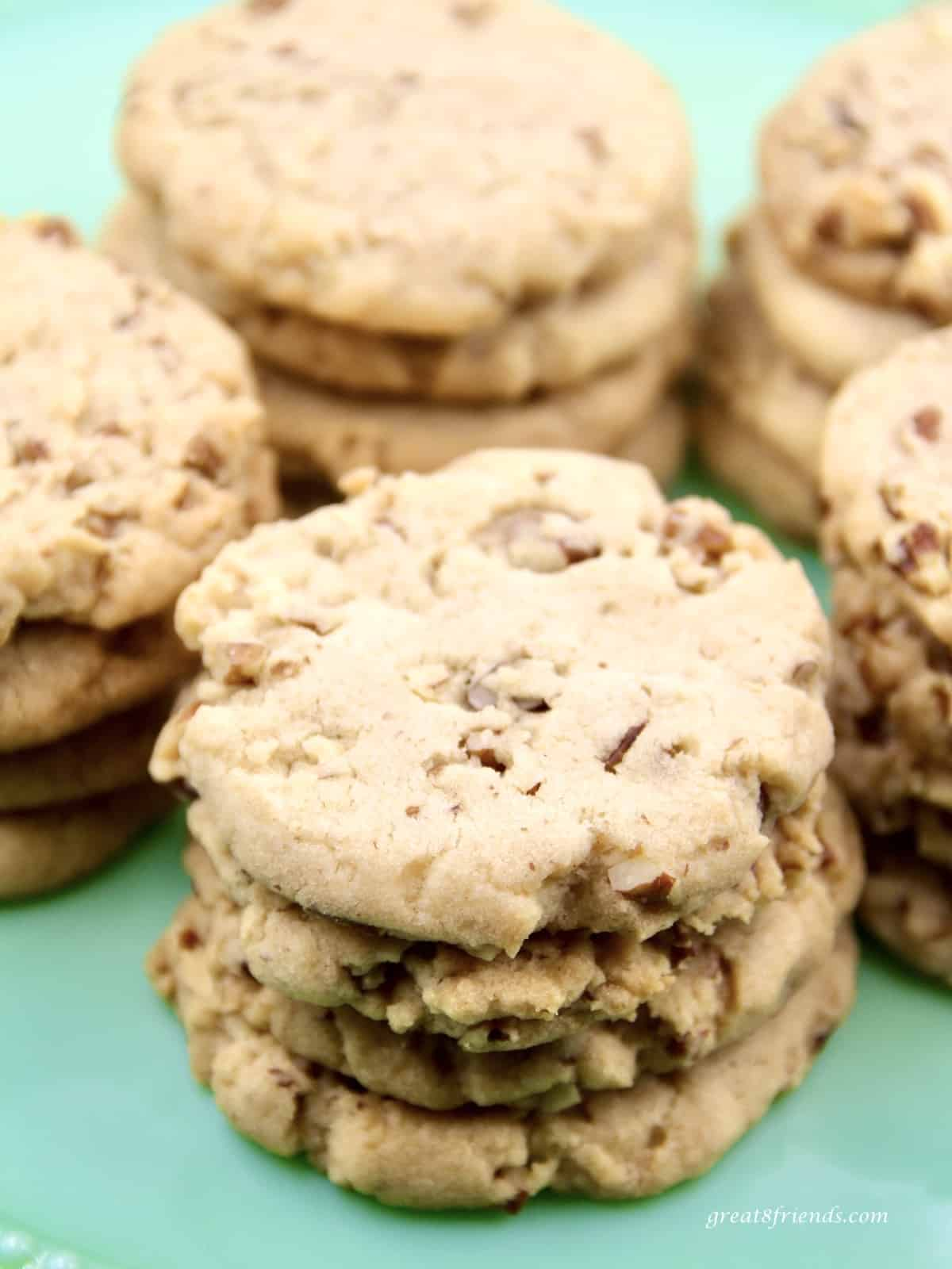 Unclose photos of pecan shortbread sandies cookies stacked on a light green plate.