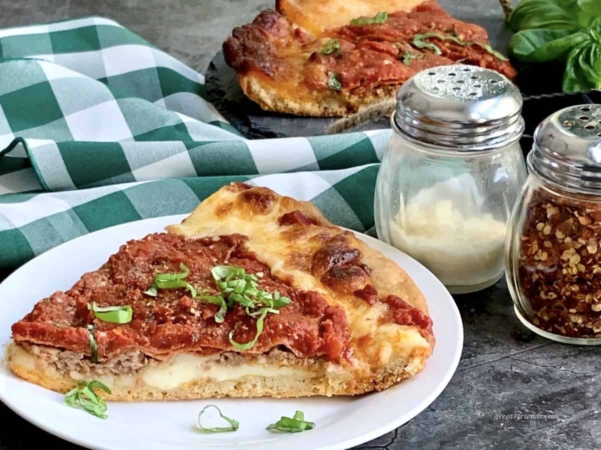 Thick chicago style pizza slice in the forefront and background with a green and white checked napkin on the table with parmesan and red pepper flakes on the side.