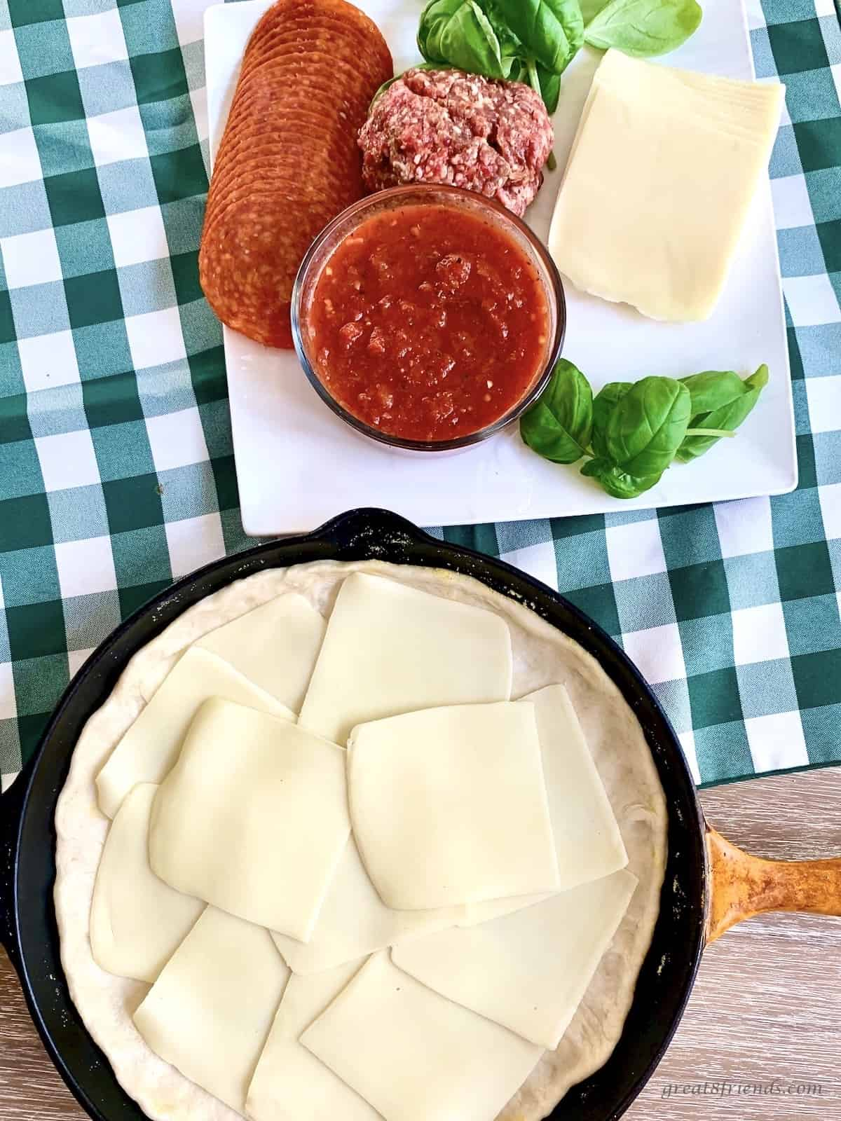 A cast iron skillet layered with pizza dough and mozzarella slices. Other ingredients on the side are pizza sauce, pepperoni, sausage, mozzarella slices and basil.