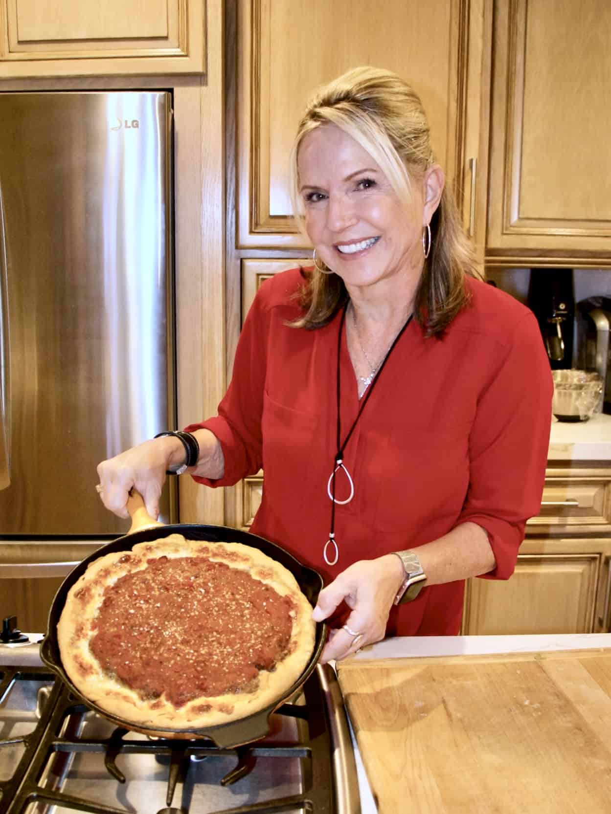 A woman wearing a red shirt showing her pizza in a cast iron skillet.