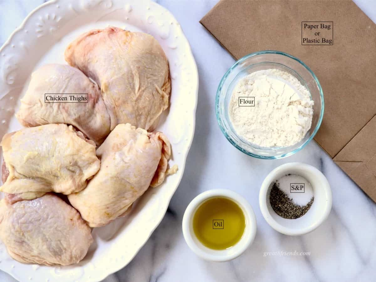 Raw chicken thighs with bowls of flour, oil and salt & pepper.