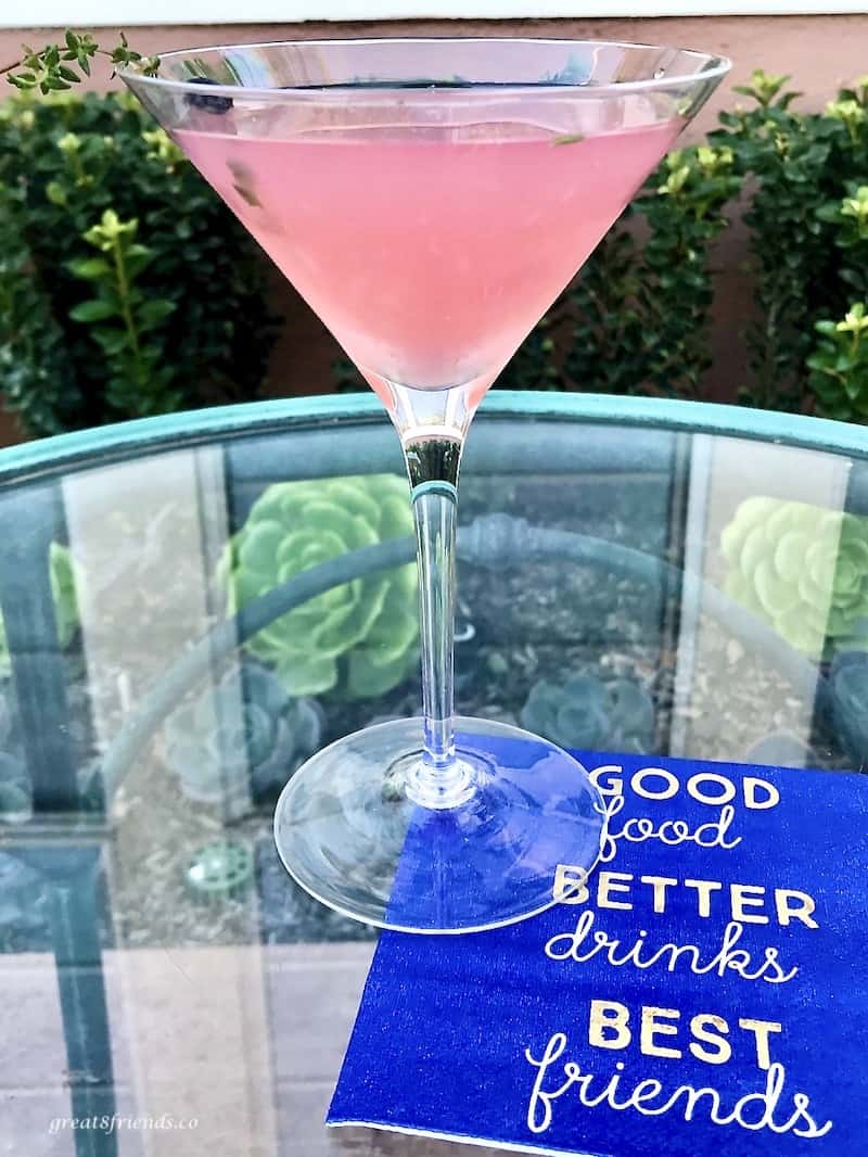 A thyme martini outside on a glass table with a royal blue napkin.
