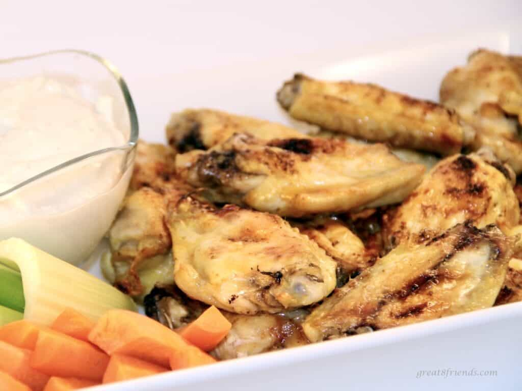 Buffalo chicken wings in a white dish served with dressing, carrots, and celery.