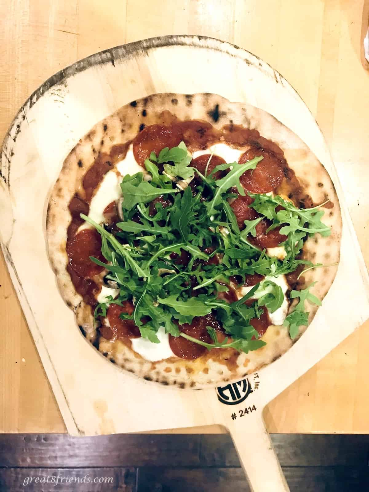 Grilled pizza with salami, cheese, pizza sauce, and arugula.